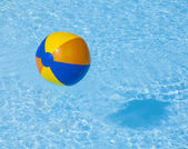 Inflated plastic ball flying in the pool — Stockfoto