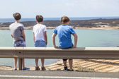 Three boys leaning at guide rail  — Stock Photo