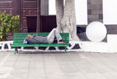 ARRECIFE, SPAIN - APRIL 3: man holds a siesta on a bench  — Stock Photo