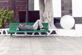 ARRECIFE, SPAIN - APRIL 3: man holds a siesta on a bench  — Stockfoto