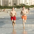 Stock Photo: Teenager enjoys jogging along beach