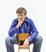 man sits on a small wooden chair and poses — Stock Photo