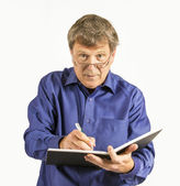 Man in blue shirt writes in his diary  — ストック写真