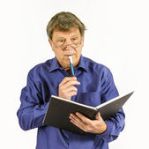 Man in blue shirt writes in his diary  — Stock Photo