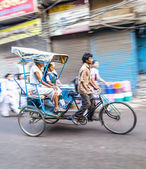 Rickshaw rider transports passenger early morning in Delhi — Stock Photo