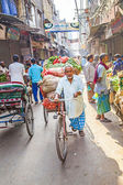 Rickshaw rider transports vegetables early morning at the market — Stock Photo