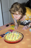 senior female blows out candles on a cake — Stock Photo