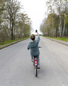 Boy shoots a picture while riding bike — Stock Photo