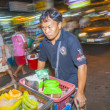 Unidentified owner of streetside rolling food stall — Stock Photo