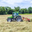 Tractor in meadow making hay — Stock Photo #46483589