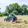 Tractor in meadow making hay — Stock Photo #46483641
