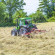 Tractor in meadow making hay — Stock Photo #46483689
