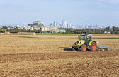 Traktor is running on the acre plowing the earth  — Stock Photo