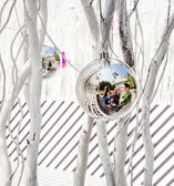 Family is mirroring in Christmas tree balls — Stock Photo