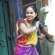Постер, плакат: Indian woman combs her hair at her home