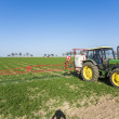 Tractor on field sputtering pest protection — Stock Photo #47592479