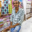 Small shop owner indian man selling shawls and clothing at his s — Stock Photo #47685193