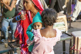 Young girl holds her baby sister in the arm at the Meena Bazaar  — Stock Photo