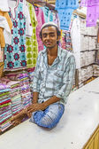 Small shop owner indian man selling shawls and clothing at his s — Stock Photo