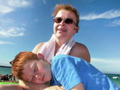 Son is relaxing on the shoulder of his mother at the beach, both — Stock Photo
