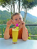 Boy drinks a fruity lemon juice in a restaurant with view to the — Stock Photo