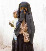 Madre desconocida árabe lleva a su bebé en una prenda envolvente — Foto de Stock