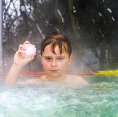 Boy enjoys swimming in the warm outdoor pool with a snowball in  — Stock Photo