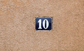 Enameled house number ten. Blue lettering on a red background.  — Stock Photo