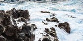 Coast with Stones of volcanic flow and ocean — Stock Photo