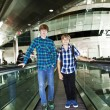 Young boys on a moving staircase inside the airport — Stock Photo #5526489