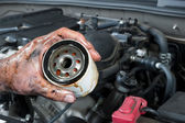 Auto mechanic holding oil filter — Foto Stock