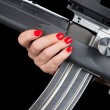 Woman holding assault rifle - Stock Photo