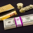 Gold bar and coins on black — Stock Photo