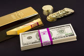 Gold bar and coins on black — Stockfoto