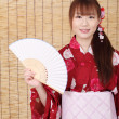 Young asian woman in kimono holding paper fan — Stock Photo