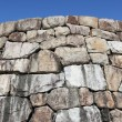 Old stone wall against clear blue sky — Stock Photo