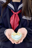 Asian schoolgirl holding a gift box — Stock Photo