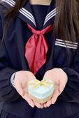 Asian schoolgirl holding a gift box — Stock Photo
