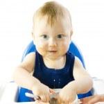 A young gray-eyed child feeding porridge — Stock Photo #12444394