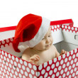 Blue eyed baby in Santa hat in present box — Stock Photo