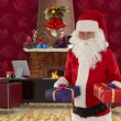 SantClaus holding presents in his modern Christmas Office — Video Stock #16839211