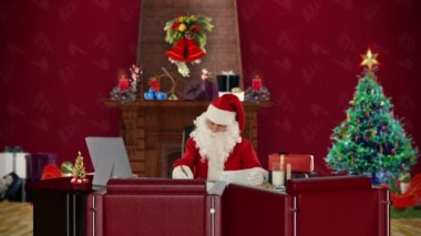 Santa Claus taking notes on a clipboard in his modern Christmas Office