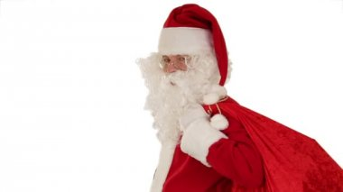 Santa Claus carrying his bag, is looking at the camera, sends a kiss and wave, white — Stock Video