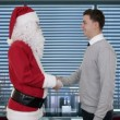 Santa Claus and Young Businessman in a modern office, shaking hands and looking at camera - Stock Photo