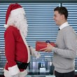 Stock video: Young Businessmreceiving present from SantClaus in modern office, shaking hands