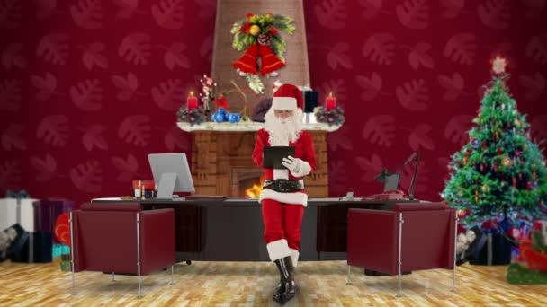 Santa claus, prendre des notes sur un presse-papiers dans son bureau de noël moderne — Vidéo