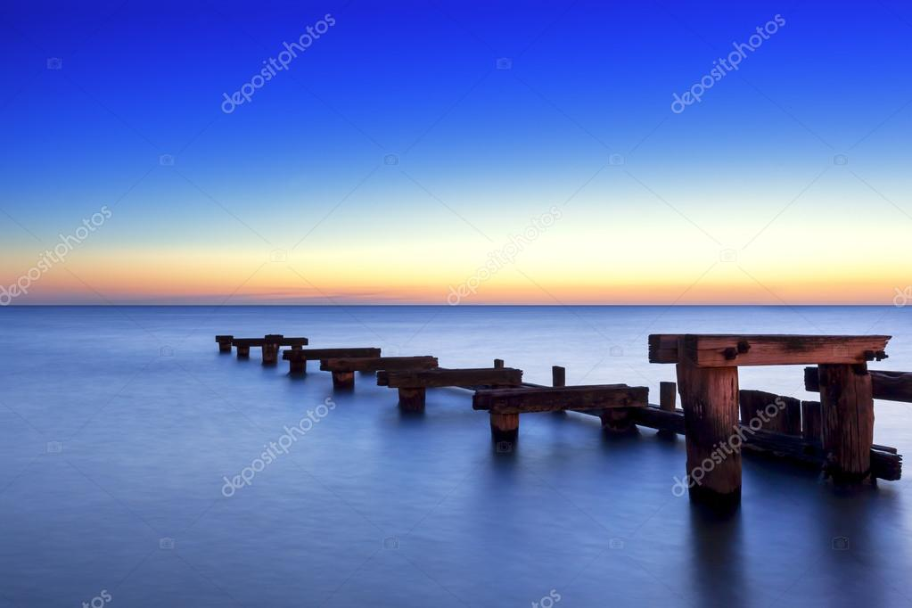 Old wooden jetty at sunset, over peaceful bay. — Stock Photo #13524303