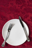 Place Setting on Red Brocade Tablecloth — Stock Photo