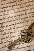 Antique Brass Key on Old Script — Stock Photo
