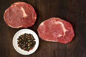 Raw Beef Steaks and Peppercorns — Stock Photo